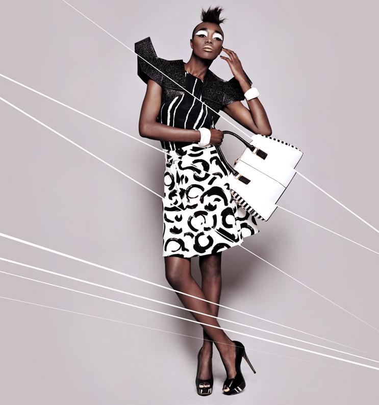 Casaco curto em neoprene metalizado com ombros geométrico Nuno Tiago, 270€; Top em crepe de seda preto e branco Mango, €19,95; Saia crepon de seda branco com pinceladas a preto Zara, €39,95; Pulseiras geométricas em madeira branca Zara, €7,95 cada; Pumps pretos com sola gráfica Aldo, psc; Carteira em pele branca com lateral em pele de riscas Aldo, psc