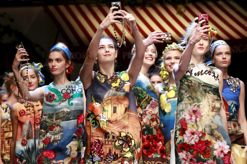 Models take selfie with mobile phones during the parade at the end of the Dolce & Gabbana Spring/Summer 2016 collection during Milan Fashion Week in Italy, September 27, 2015.  REUTERS/Alessandro Garofalo       TPX IMAGES OF THE DAY